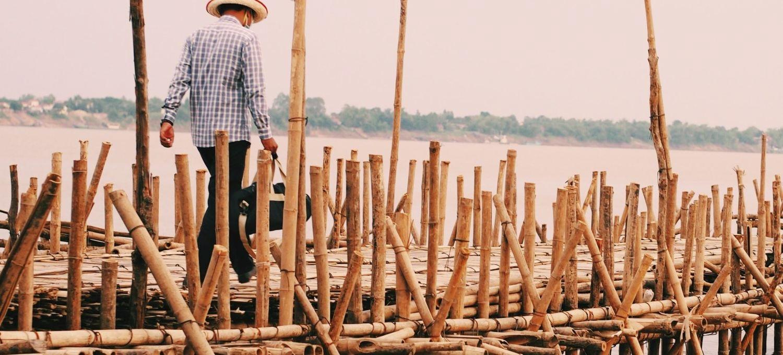Man-walking-on-the-bamboo-bridge-min